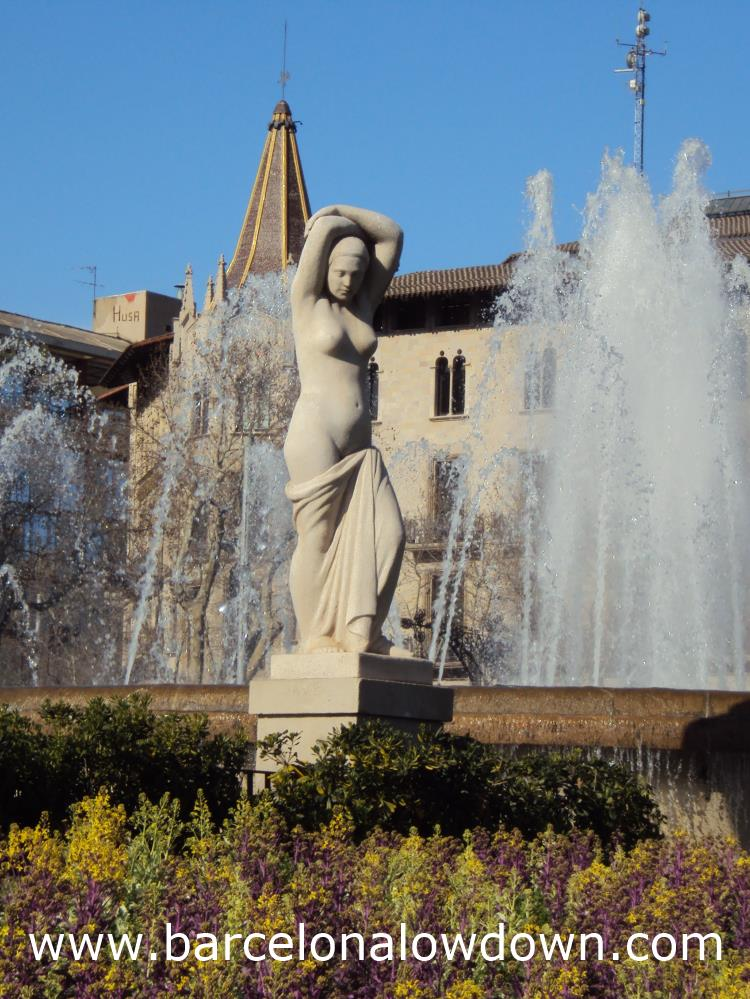 Youth - Statue by Josep Clarà set between flowers and a fountain