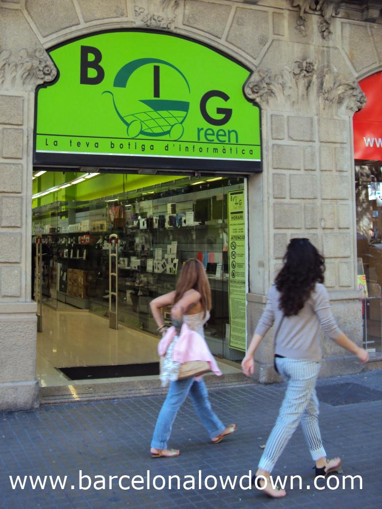 2 girls walking past a computer store in Barcelona