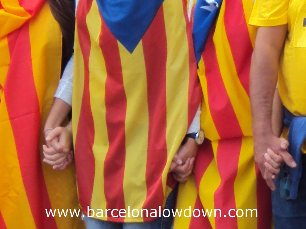 "Catalans dressed in Catalan independence flags holding hand as part of the 400km long ""Catalan Way"" in Barcelona"