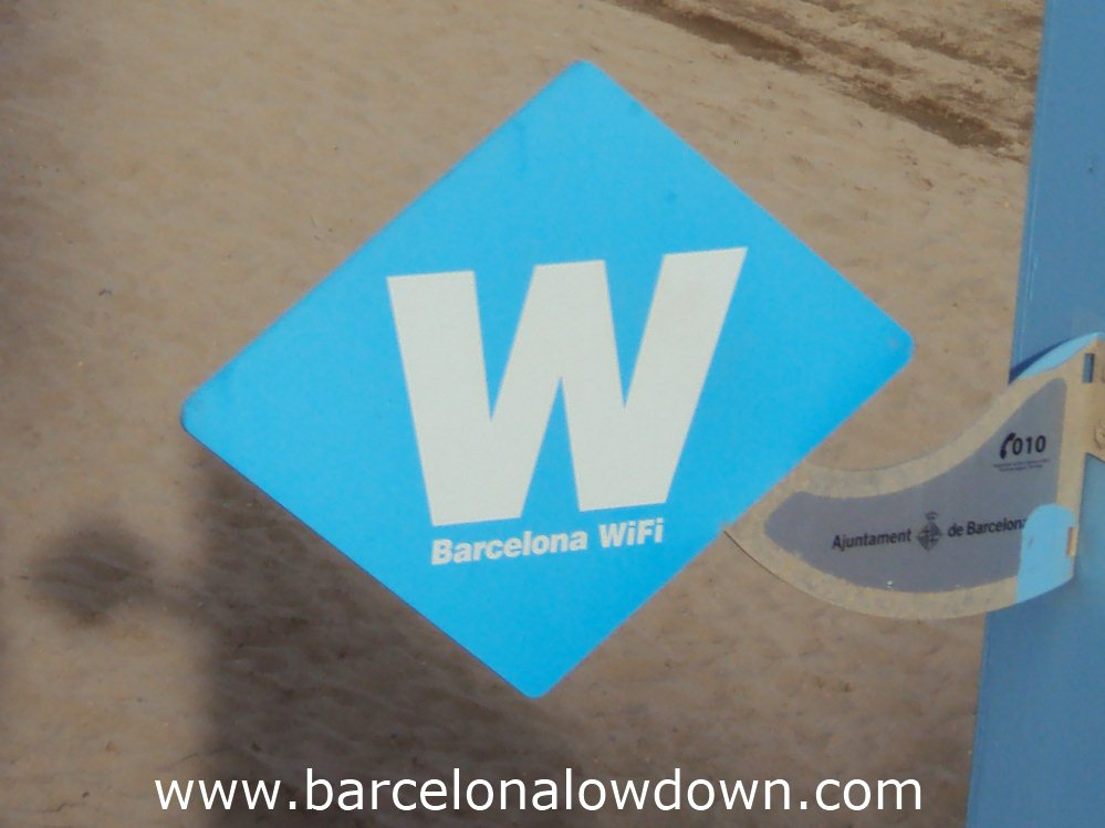 Blue W sign indicating a free Barcelona WIFI hotspot on the Barceloneta beach.