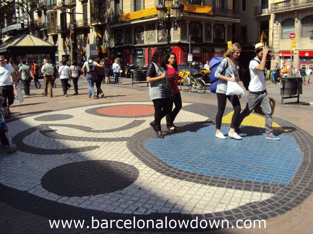 Tourists walking over Miro's famous mosaic on the Ramblas pedestrianised avenue in central Barcelona