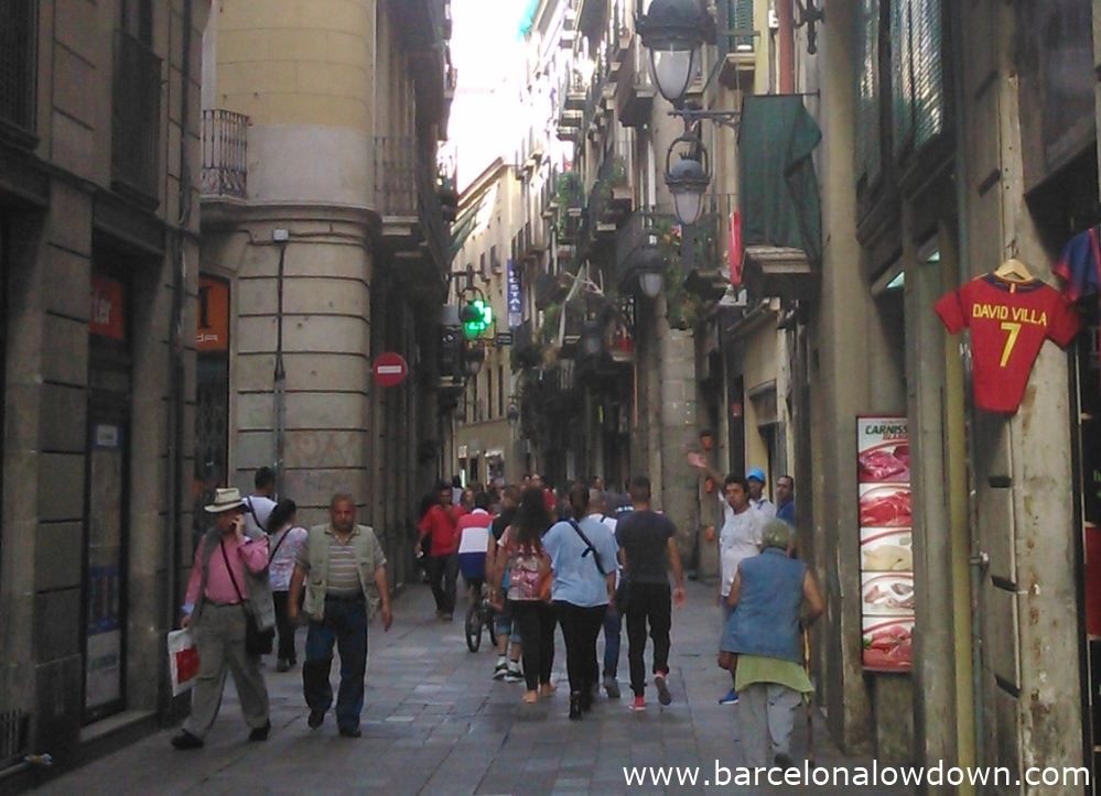 A typical narrow crowded street in Barcelonas colourful Raval neighbout¡rhood.