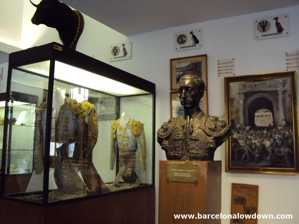 A bronze statue of famous Spanish bullfighter Manolete, 2 bullfighters' costiumes in a glass cabinet, a stuffed bulls' head and various old photos in the bullfighting museum located in the Plaza de Toros Monumental bulring Barcelona, Spain