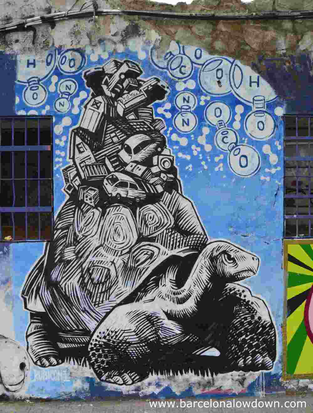 Graffiti in Poblenou, BCN. Painting of an angry looking tortoise carrying a ton of cars and trucks on his back.