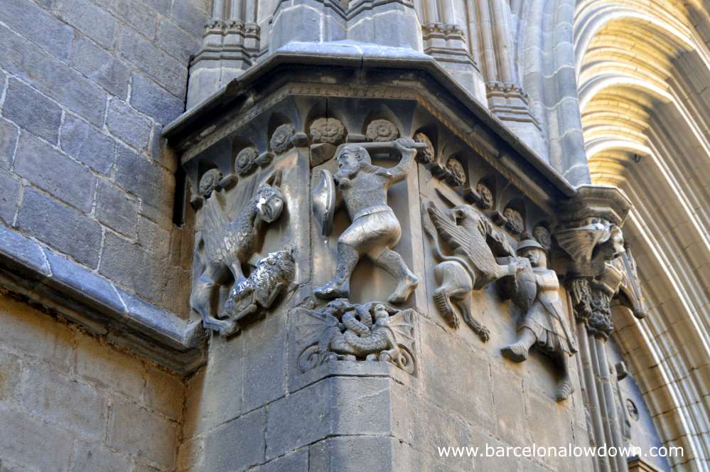 Stone carving of Wilfred the Hairy slaying a dragon with a wooden staff next to the door of Barcelona cathedral