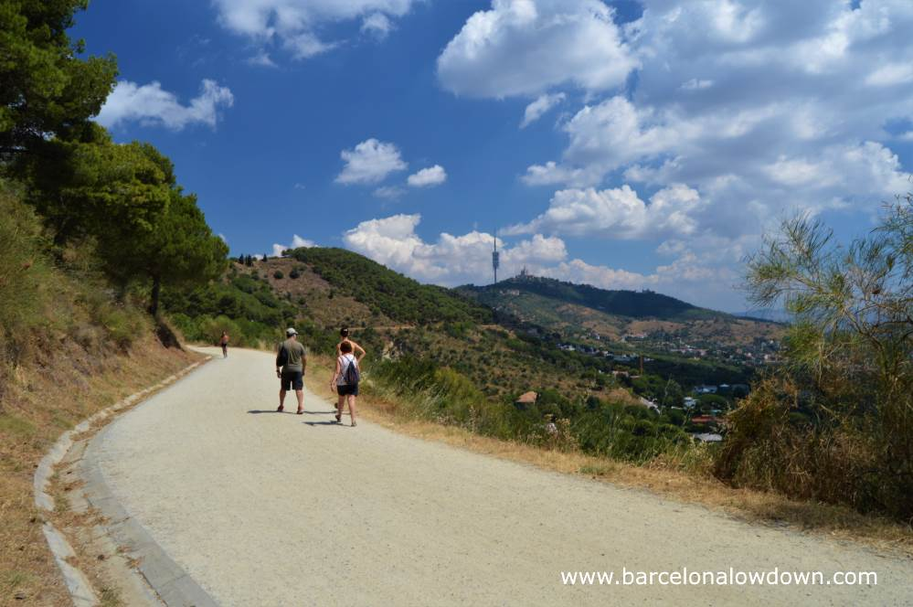 A group of friends walking the Carretera de les aigues walking trail in Collserola national park Barcelona