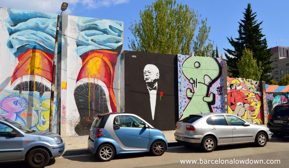 Streetart wall in Barcelona. There are 4 paintings behind some parked cars. The most notable painting shows corrup politician and Ex President of Catalonia Jordi Pujol portrayed as the Godfather.