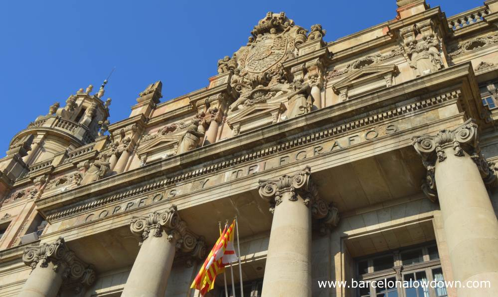 Close-up of the carvings above the main entrance to Barcelona Central Post Office. There is a large coat of arms and several stone statues above the greek style entrance way with decorated columns. At the bottom of the photo there are two flags one is the Catalan flag the other is the flag of Barcelona.