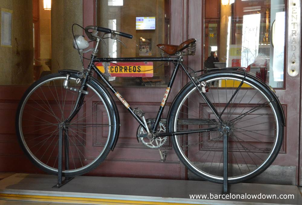 One of the two black vintage postman's bikes located just inside the entrance of Barcelona Central Post Office. The bike is standing in front of brown doors with windows through which you can see the interior of the post office.