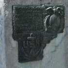 Metal plaque on the base of the monument with and inscription and an anchor and eagle