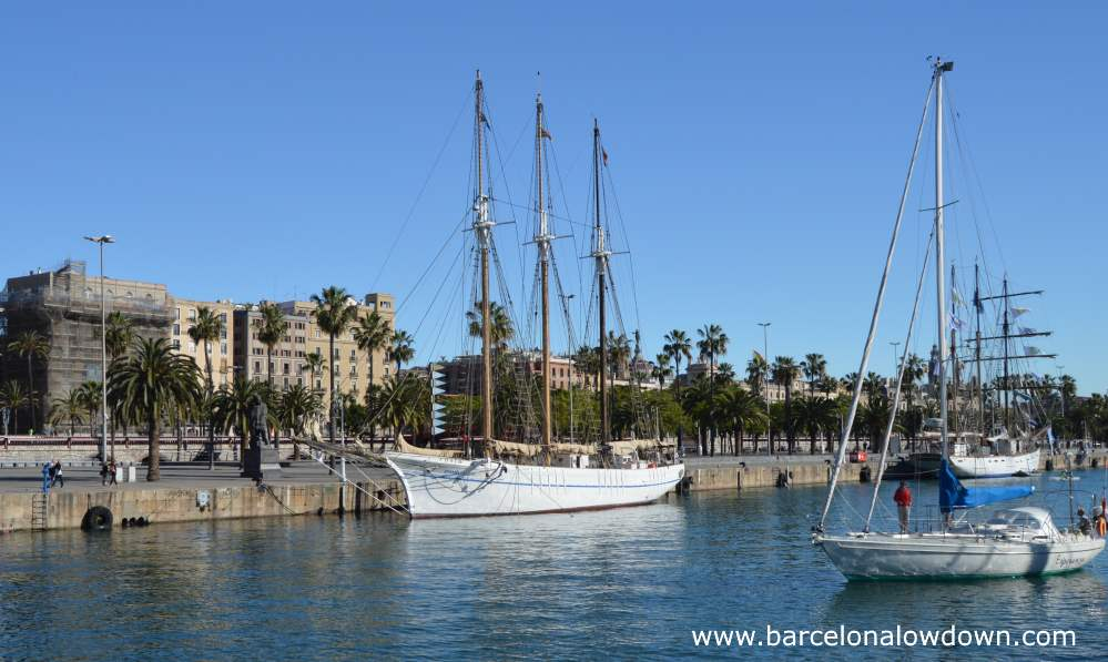 Monument to Joan Salvat i Papasseit and tall ships on the waterfront at Barclona harbour