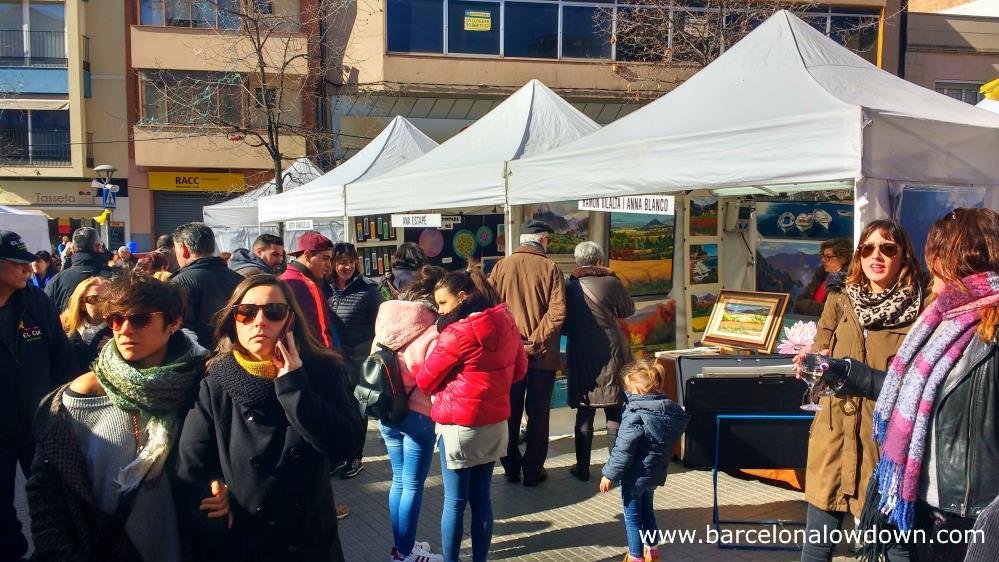 Market stalls selling colorful paintings at the Fira de la Candelera fair in Molins de Rei Barcelona Spain