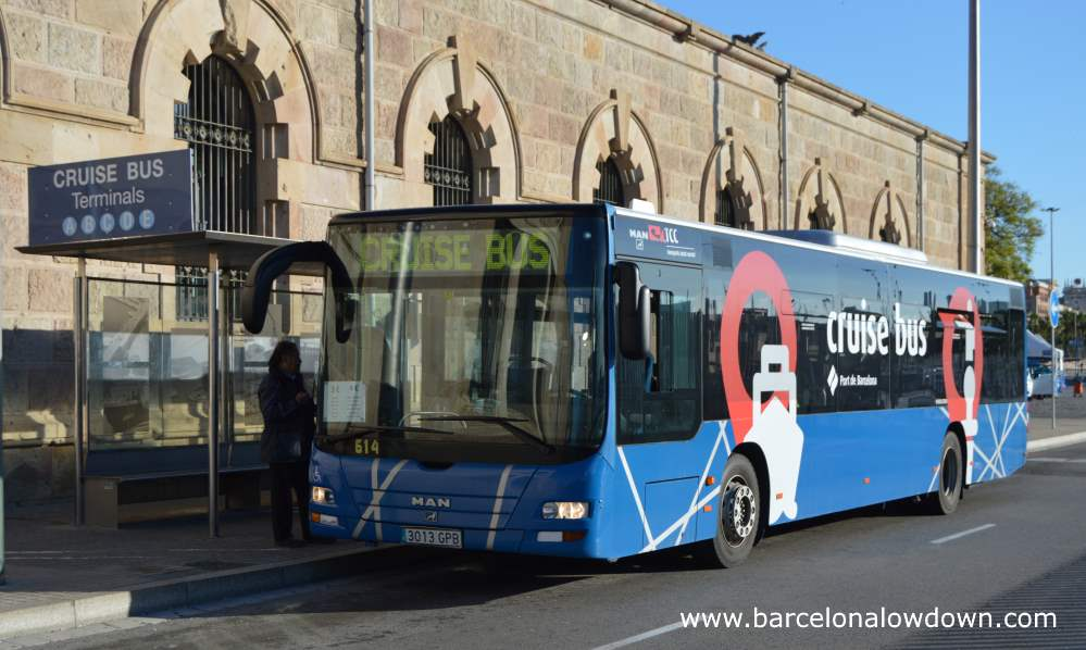 a blue cruise ship shuttle bus parked at a bus stop next to Barcelona harbour