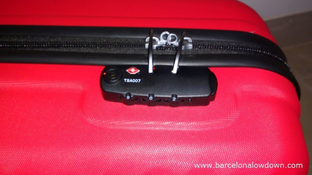 A locked red suitcase with a TSA007 combination lock