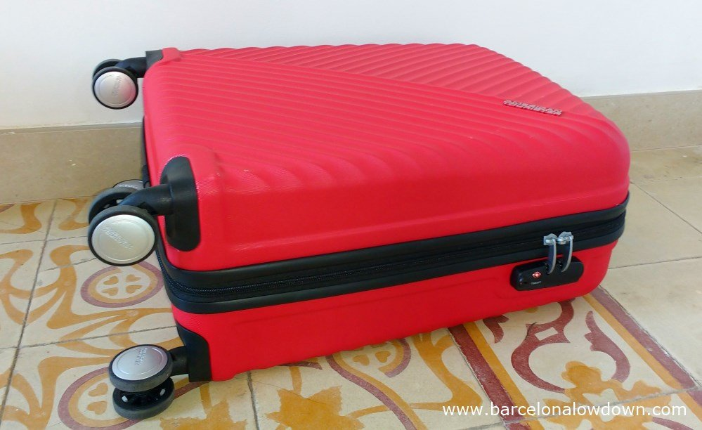 A red hand luggage size American Tourister suitcase with a built in combination lock