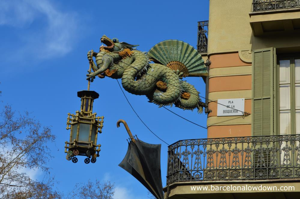 The painted steel Chinese dragon sign on the façade of the umbrella house Barcelona. The dragon is adorned by a fan, an umbrella and a bamboo lantern.