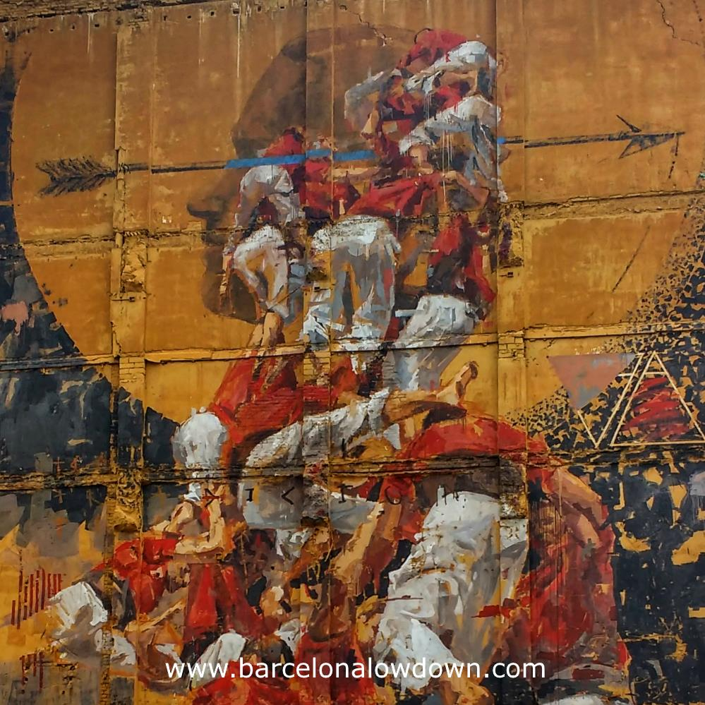 Closeup photo of the painting Fer Llenya. The painting shows a group of Castellers in the moment that the tower collapses. The background of the painting is the siluette of a person whose head is traversed by an arrow.